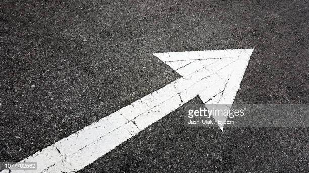 high angle view of arrow symbol on road - arrow stock pictures, royalty-free photos & images