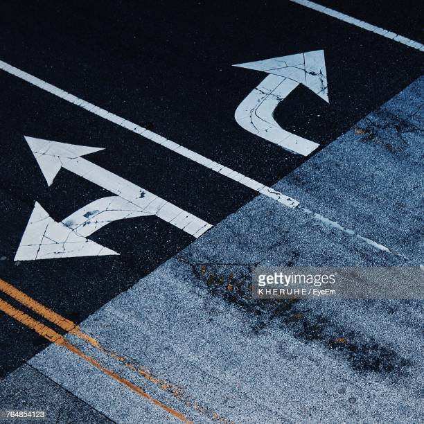 high angle view of arrow symbol on road - dividing line road marking stock pictures, royalty-free photos & images