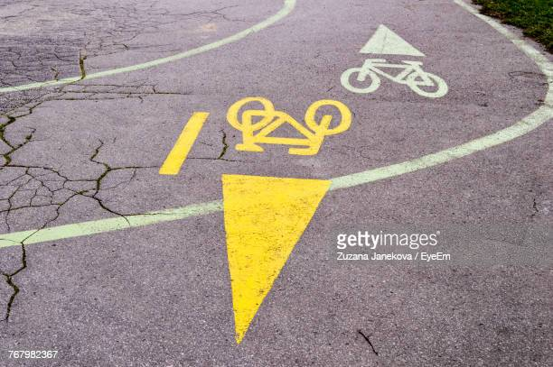 high angle view of arrow symbol on road - zuzana janekova stock pictures, royalty-free photos & images