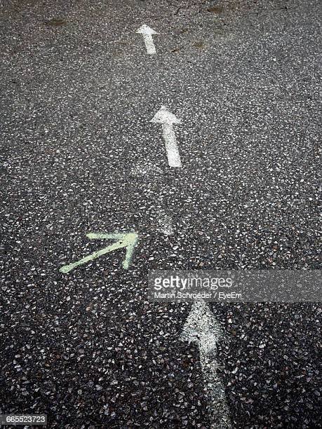 High Angle View Of Arrow Symbols On Road