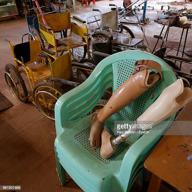 High Angle View Of Artificial Legs On Chair By Wheelchairs