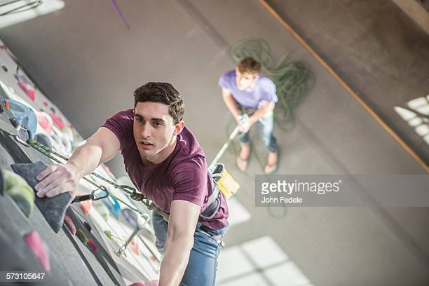 High angle view of athlete climbing rock wall in gym
