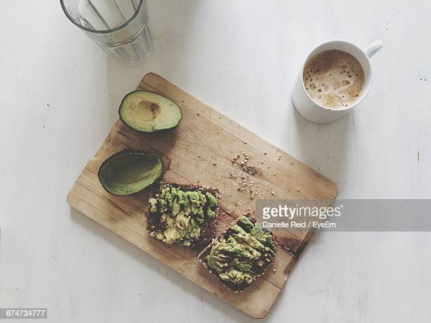 High Angle View Of Avocado And Breads By Coffee Cup On Cutting Board Over Table