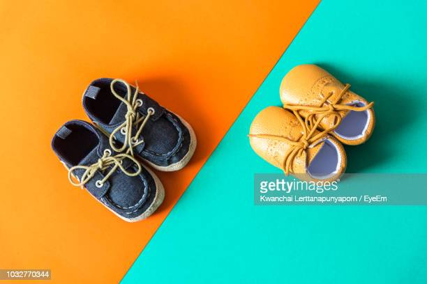 high angle view of baby booties over colored background - orange shoe stock photos and pictures