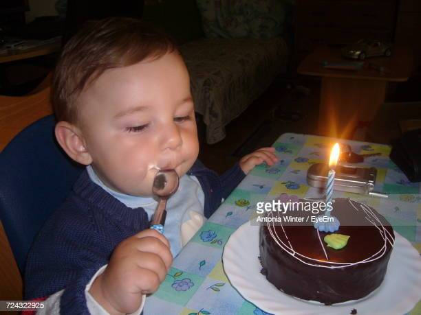 High Angle View Of Baby Boy With First Birthday Cake At Table