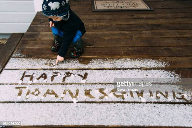 high angle view of baby boy writing thanksgiving text with snow on floor - happy thanksgiving text stock pictures, royalty-free photos & images