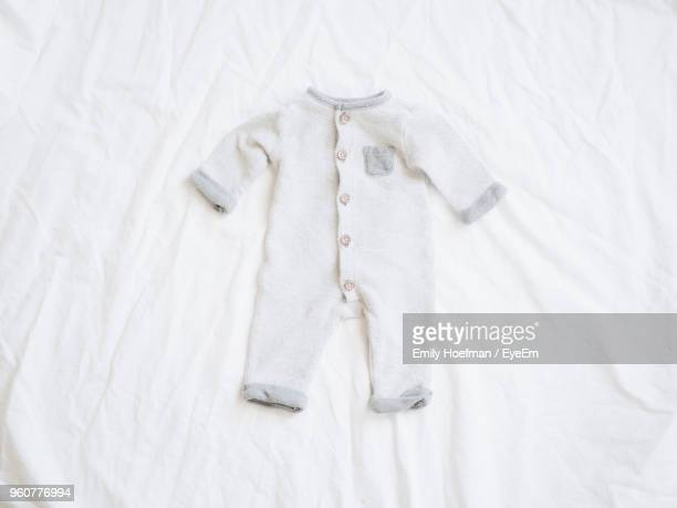 High Angle View Of Baby Clothing On Bed