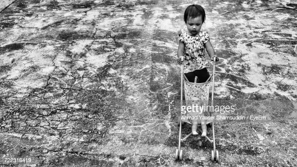 High Angle View Of Baby Girl Pushing Doll In Stroller On Footpath