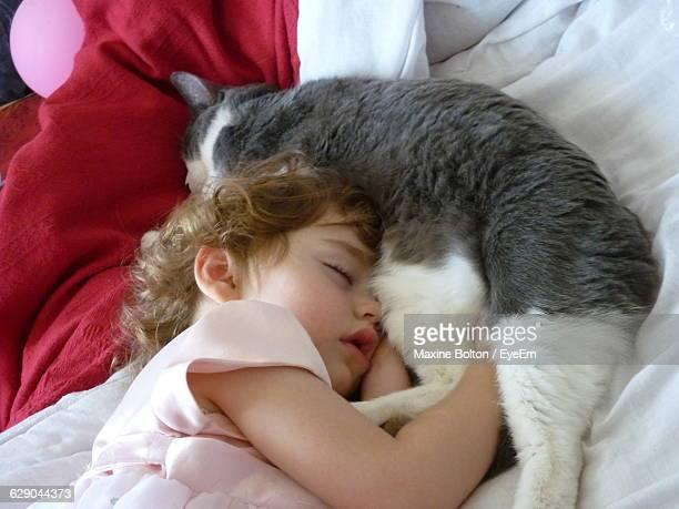 High Angle View Of Baby Girl Sleeping With Cat On Bed At Home