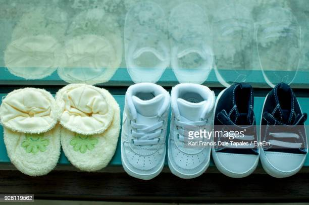 high angle view of baby shoes on window sill - baby booties stock photos and pictures
