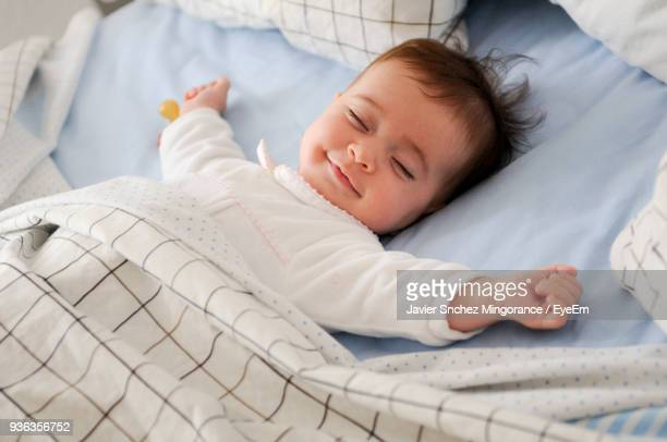 high angle view of baby sleeping on bed at home - slapen stockfoto's en -beelden