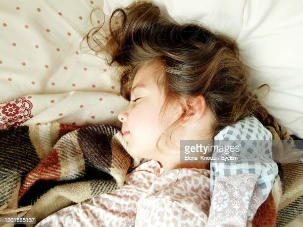high angle view of baby sleeping on bed - elena knouzi stock pictures, royalty-free photos & images