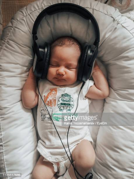 high angle view of baby sleeping with headphones on bed - babyhood stock pictures, royalty-free photos & images