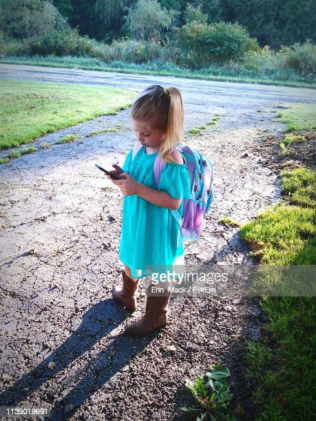 high angle view of backpack girl using phone on footpath - mack stock pictures, royalty-free photos & images