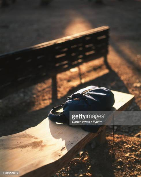 High Angle View Of Backpack On Wooden Bench During Sunset