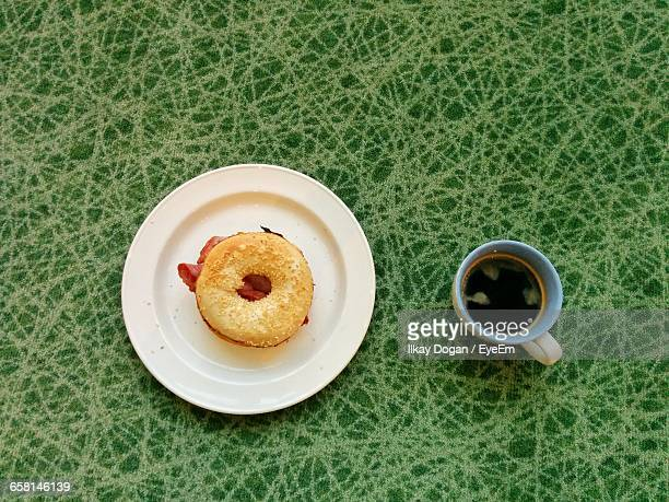 High Angle View Of Bagel In Plate And Coffee Cup On Rug