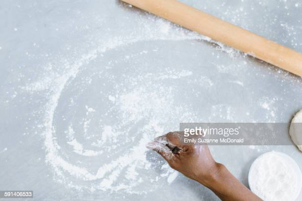 High angle view of baker sprinkling flour on counter