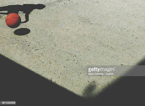 High Angle View Of Ball And Shadow On Street