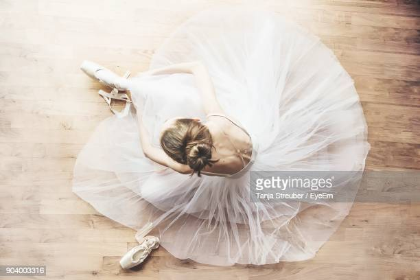 high angle view of ballerina sitting on hardwood floor - バレリーナ ストックフォトと画像