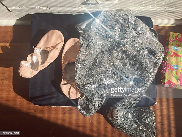 High Angle View Of Ballet Shoes And Sequins Cloth On Floorboard