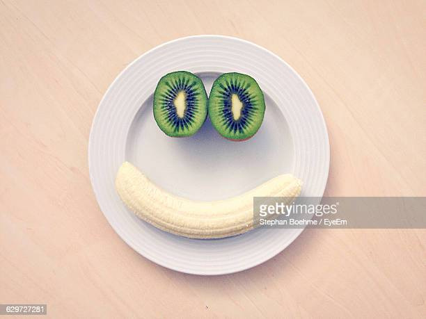 High Angle View Of Banana And Kiwi In Plate On Table