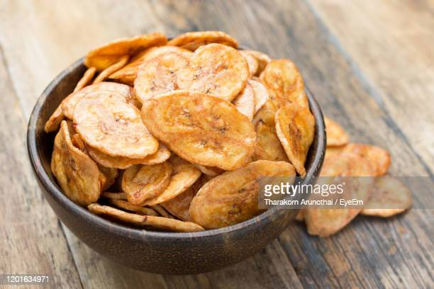 high angle view of banana chip in bowl on table - fried stock pictures, royalty-free photos & images