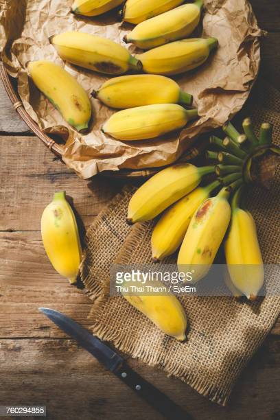 High Angle View Of Bananas With Burlap And Knife On Wooden Table