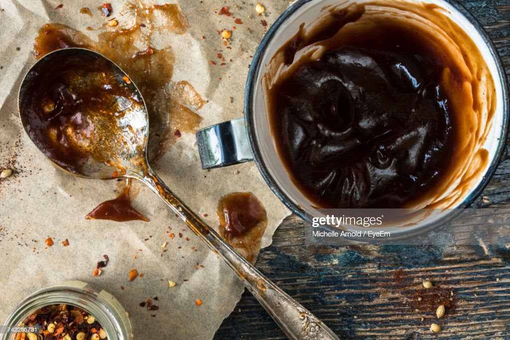 High Angle View Of Barbeque Sauce In Bowl By Spoon On Table : Stock Photo