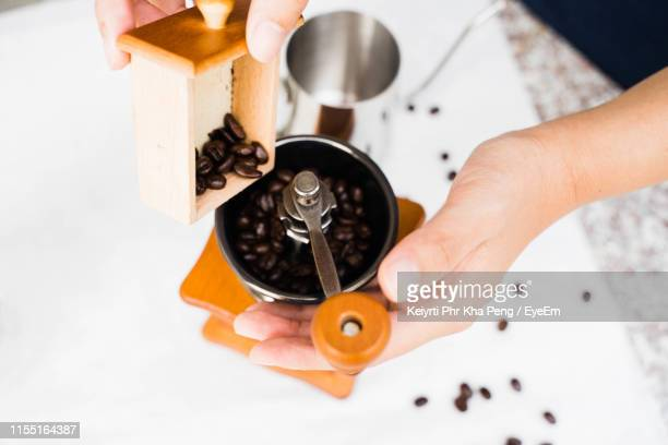 high angle view of barista grinding roasted beans in coffee grinder - coffee grinder stock photos and pictures