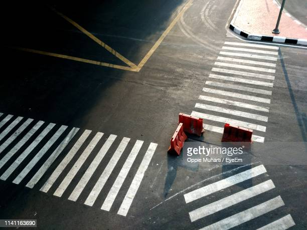high angle view of barricades at zebra crossing on road - traffic cone stock pictures, royalty-free photos & images