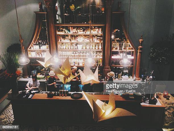 High Angle View Of Bartenders At Illuminated Counter