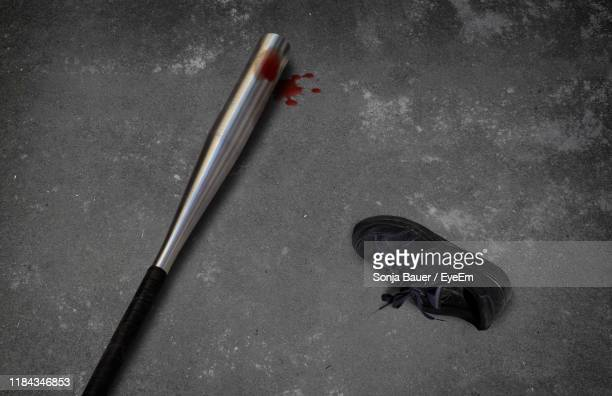 high angle view of baseball bat with blood by shoe on floor - baseball bat stock pictures, royalty-free photos & images