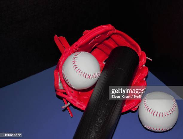 high angle view of baseball gear on table against black background - eileen kirsch stock pictures, royalty-free photos & images