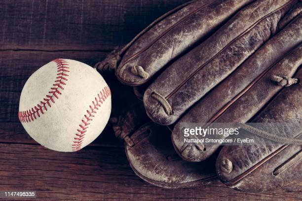 high angle view of baseball glove and ball on table - baseball glove stock pictures, royalty-free photos & images
