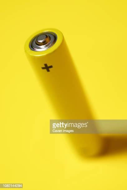 high angle view of battery on yellow background - signo de más fotografías e imágenes de stock