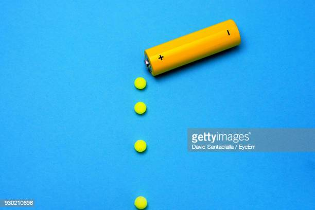 high angle view of battery with balls on blue background - battery stock photos and pictures