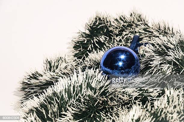 High Angle View Of Bauble And Tinsel Over White Background