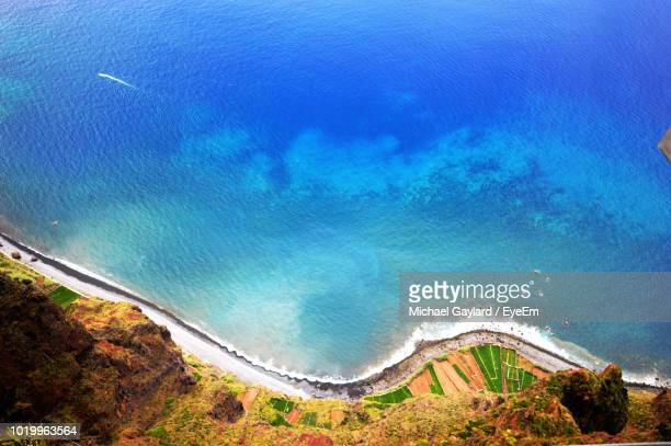 high angle view of bay against blue sky - madeira island stock photos and pictures