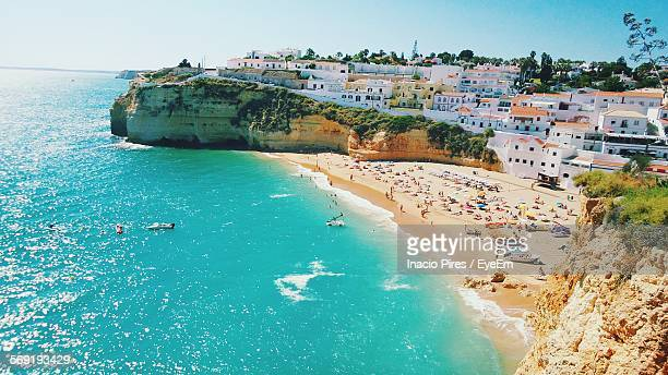 high angle view of beach and houses at carvoeiro against clear sky - algarve stock photos and pictures