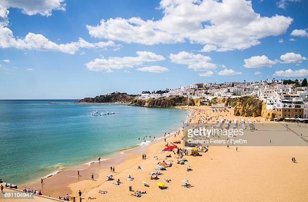high angle view of beach by houses against cloudy sky - algarve fotografías e imágenes de stock