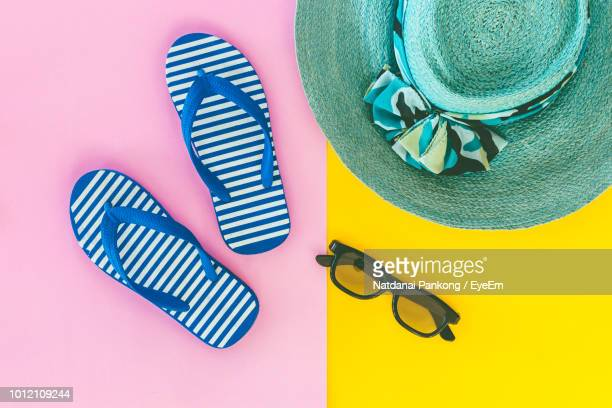 high angle view of beach supplies over colored background - ciabatta infradito foto e immagini stock