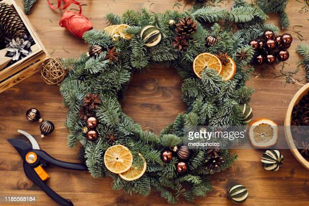 high angle view of beautiful holiday wreath decorated orange slices, fir tree cones and small balls placed on wooden table among decorations and tools - wreath stock pictures, royalty-free photos & images
