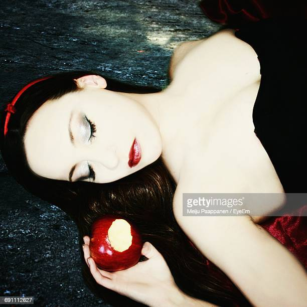 High Angle View Of Beautiful Woman In Costume Holding Apple While Lying On Footpath