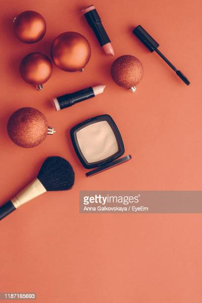high angle view of beauty products and christmas decoration on orange background - christmas still life stock pictures, royalty-free photos & images