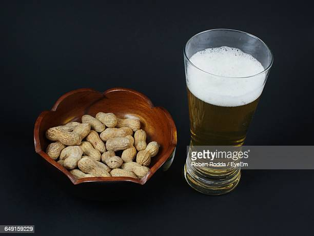 High Angle View Of Beer And Peanuts Against Black Background