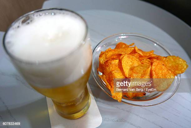 High Angle View Of Beer And Potato Chips On Table