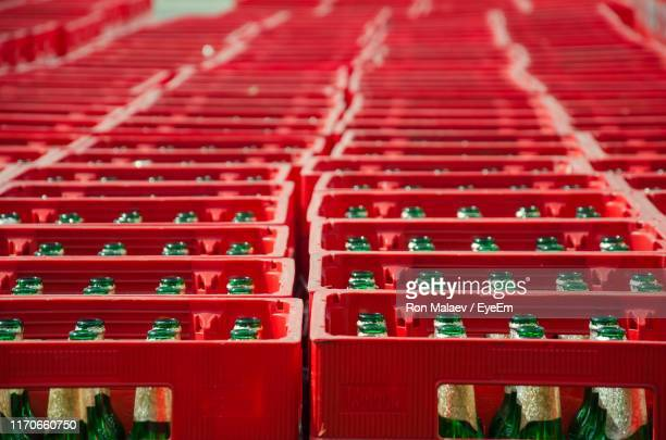 high angle view of beer bottles in crates for sale - holzkiste stock-fotos und bilder