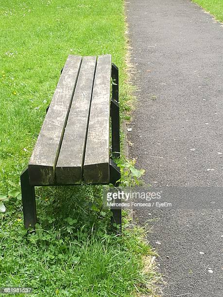 High Angle View Of Bench On Field By Footpath