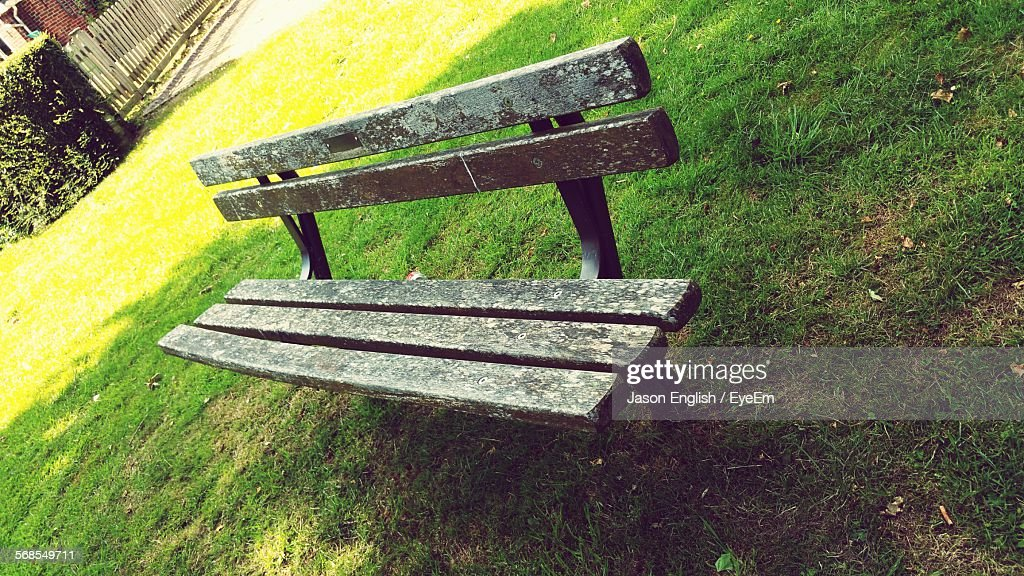 High Angle View Of Bench On Grassy Field At Park : Stock Photo