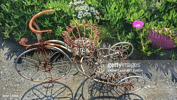 High Angle View Of Bicycle Shaped Metal By Plants On Road